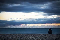 Offshore wind farm at dusk viewed from the beach stock photos