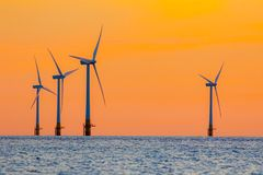 Offshore wind farm energy turbines at dawn. Surreal but natural. Sunrise at sea. Modernistic image. The future of clean energy production Stock Images