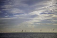 Offshore wind farm on horizon with calm sea. The subtle subdued nature of this picture reflects the ethos of sustaniable energy via the gentle giants that are Stock Image