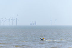 Offshore wind farm and speed boat Stock Images