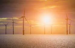 Offshore Wind Turbine in a Wind farm under construction off coast of England at sunset. royalty free stock photo