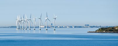 Offshore wind turbines on the coast of Copenhagen in Denmark with the airport in the background royalty free stock photo