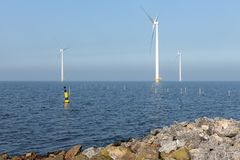 Offshore wind turbines near Dutch coast with buoy. Sunny day with offshore wind turbines near Dutch coast with buoy and poles for fishing nets royalty free stock photo