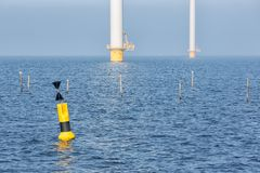 Offshore wind turbines near Dutch coast with buoy. Sunny day with offshore wind turbines near Dutch coast with buoy and poles for fishing nets royalty free stock image