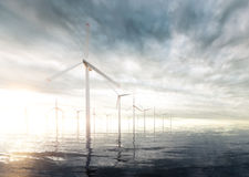 Offshore wind turbines with sunset stormy sky in background Stock Images
