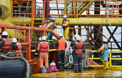 Offshore working on deck. Deck crew standby on deck during crew transfer using swing rope with oil platform stock photography