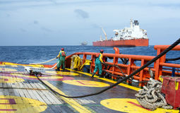 Offshore working on deck. Deck crew standby on deck during static tow operation with crude oil tanker at sea stock photo
