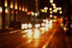 Offuschi il bokeh di luce sulla via di traffico nel BAC scuro della città di notte fotografia stock