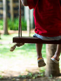 Offuschi il pic del bambino che si siede sull'oscillazione in giardino Fotografia Stock Libera da Diritti