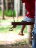 Offuschi l'immagine del bambino che si siede sull'oscillazione in giardino fotografia stock
