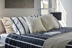 Offwhite и striped подушки на кровати Стоковое Изображение