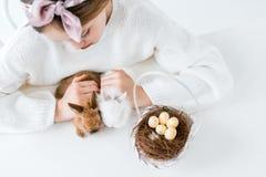 Ofgirl cultivé de tir regardant les lapins et le panier velus mignons avec des oeufs de pâques dans le nid Photo stock