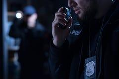 Oficer używa walkie talkie Fotografia Stock