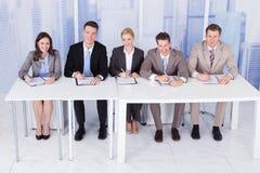 Oficiais de pessoais incorporados que sentam-se na tabela Fotos de Stock