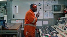 Oficial africano del ingeniero marino en el ECR de la sala de control del motor almacen de video