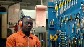 Oficial africano del ingeniero marino en el ECR de la sala de control del motor almacen de metraje de vídeo