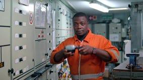 Oficial africano do coordenador marinho no ECR da sala de comando do motor video estoque