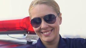 Oficial amigável de sorriso da senhora nos vidros que olham à câmera, segurança social video estoque