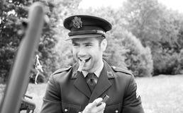 Oficial de ejército hermoso del SOLDADO ENROLLADO EN EL EJÉRCITO del americano WWII en cigarro que fuma uniforme al lado de Willy foto de archivo libre de regalías