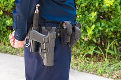 Oficial de ley Standing Guard con el arma y el bastón en la correa Fotos de archivo