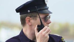 Oficial de patrulha masculino que fala no rádio, transportando a informação em relação ao criminoso video estoque