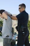 Oficial de policía Arresting Young Man Fotos de archivo libres de regalías