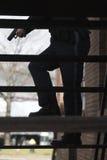 Oficial de policía con la búsqueda exhausta de la pistola. Fotografía de archivo