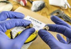 Oficial de policía experto que compara dos nueve milímetros de balas en laboratorio de la balística imagen de archivo