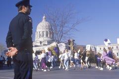 Oficial de policía observando la marcha proabortista Imagen de archivo libre de regalías