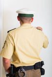 Oficial de policía que golpea en puerta principal Fotos de archivo