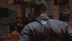 Oficial de policía de sexo masculino que mira al tablero de la investigación, imaginando el lugar del peligro almacen de video