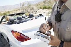 Oficial de policía Writing Traffic Ticket a la mujer que se sienta en coche Foto de archivo libre de regalías