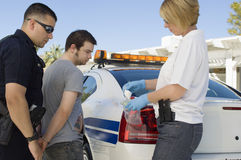Oficial de policía Arresting Young Man Imagen de archivo
