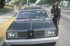 Oficial de policía de tráfico que marca al conductor femenino, Santa Monica, California Foto de archivo libre de regalías