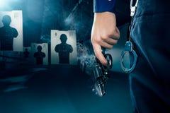 Oficial de policía que sostiene un arma en una radio de tiro/un ligh dramático Fotos de archivo