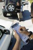 Oficial de policía Writing Ticket Foto de archivo libre de regalías