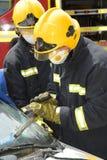 Oficial del fuego que corta un parabrisas en el choque del coche Fotos de archivo