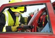 Oficial del fuego que corta un tejado del coche en el choque del coche Imágenes de archivo libres de regalías