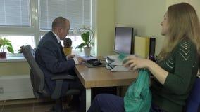 Oficial del vendedor en mirada del traje en los documentos de la mujer del cliente 4K almacen de metraje de vídeo