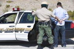 Oficial maduro Arresting Man del tráfico Imagen de archivo