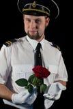 Oficial que da la rosa Imagen de archivo libre de regalías