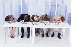 Oficiales de personales corporativos cansados en la tabla Imagen de archivo libre de regalías