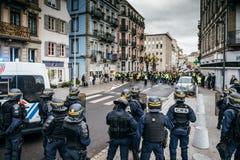 Oficiales de policía que aseguran la zona delante de las chaquetas amarillas Gil foto de archivo libre de regalías
