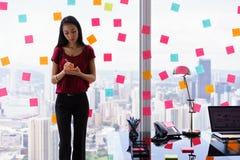 Oficina caótica con secretaria Writing Sticky Notes en ventana fotografía de archivo