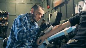 Oficina com um artista masculino que tattooing um braço protético video estoque