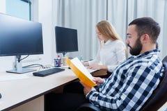 Oficina con los trabajadores que se están sentando en los ordenadores imagen de archivo