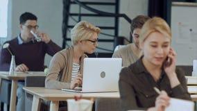 Oficina conceptora ocupada con los trabajadores en los escritorios almacen de metraje de vídeo