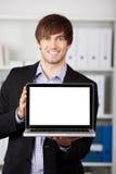 Oficina de Displaying Laptop In del hombre de negocios foto de archivo libre de regalías