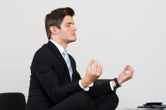 Oficina de Doing Meditation In del hombre de negocios imagenes de archivo