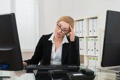 Oficina de Having Headache In de la empresaria fotos de archivo libres de regalías